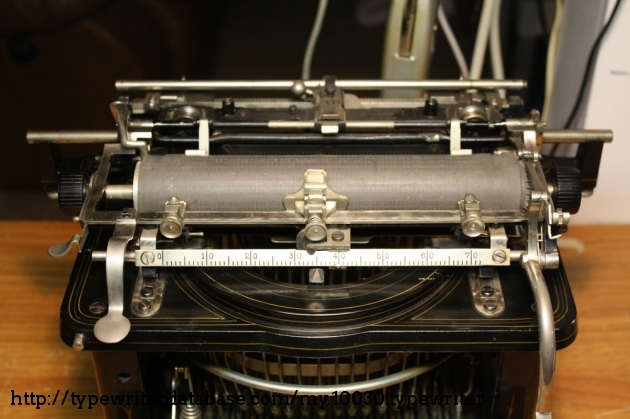 A large carriage covered in rods and levers. To accomplish shifting, this typewriter shift's its carriage back and forth instead of up and down.
