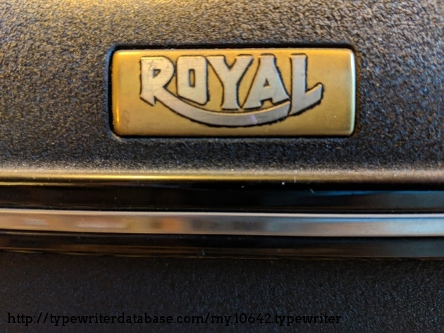 Detail of gold nameplate / head-badge with accent trim.