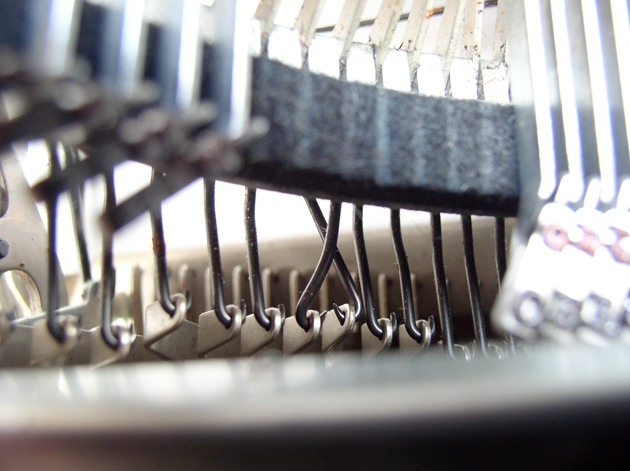 This is a pic of a curious arrangement of crossed linkages, the X and the E keys, in an Olivetti-Underwood 21. Why is this done this way? Some engineer screwed up?
