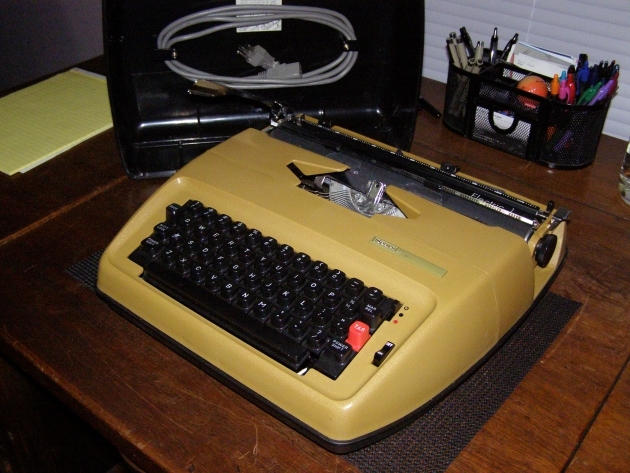 "See how the cord is cleverly mounted to the top of the inside of the case.  Also the bottom of the ""case"" is the bottom on the typewriter itself.  Hence the high ""waterline"" (like on a ship) that kind of slims the design by being two tone..."