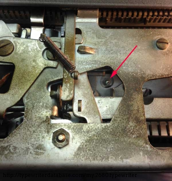 View of the back of the typewriter, with panel off. Turning this screw counterclockwise fixed the skipping problem. Get access to the retaining nut by slipping needlenose pliers through the bottom of the machine.