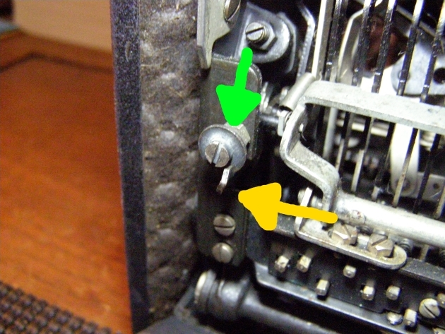 Yellow arrow points toward a catch attached to the carriage which is pushed back when the shift key is pressed, the green arrow points to a disc the catch hooks onto.  This keeps the carriage from bobbing with the vibrations in a ship or an airplane.
