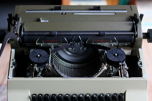 Removing the ribbon cover shows this typewriter to be a straight descendant of the Optima M10, M14, etc: there's lots of stowing space on the sides of the mechanism
