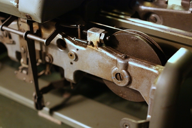 The mainspring wheel, under the carriage. To its left the stop that, together with another one on the other end of the machine, sets the line lock (see next image)