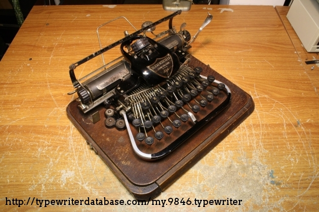 The typewriter at an angle. The replacement left roller and bracket are visible.